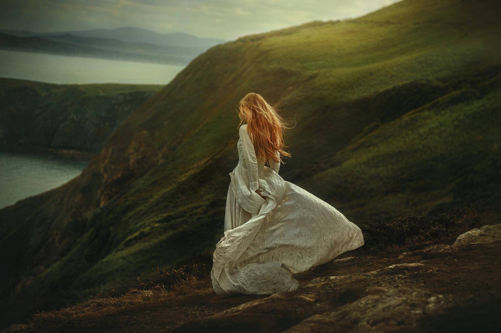 women_model_redhead_white_dress_hills_cliff_coast_emotion-109003